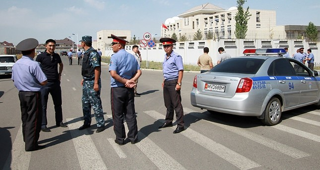 Investigators, Interior Ministry officers and members of security forces gather near the site of a bomb blast outside China's embassy in Bishkek, Kyrgyzstan (Reuters Photo)