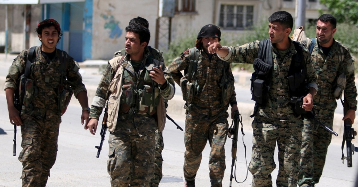 YPG terrorists walk along a street in the southeast of Qamishli city, Syria, April 22, 2016 (Reuters File Photo)