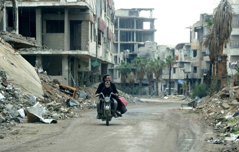 A Syrian man drives past destroyed buildings in Arbin, Syria, Dec. 18.