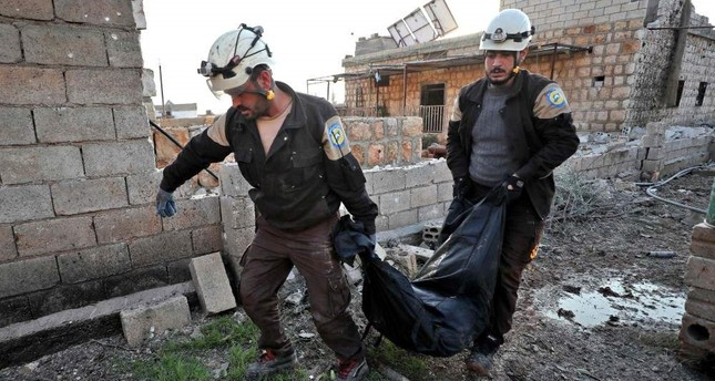 Members of the Syrian Civil Defense, also known as the White Helmets, carry the body of a victim after reported Russian airstrikes in Maar Shimmareen village in Syria's northwestern Idlib province on Dec. 16, 2019. AFP