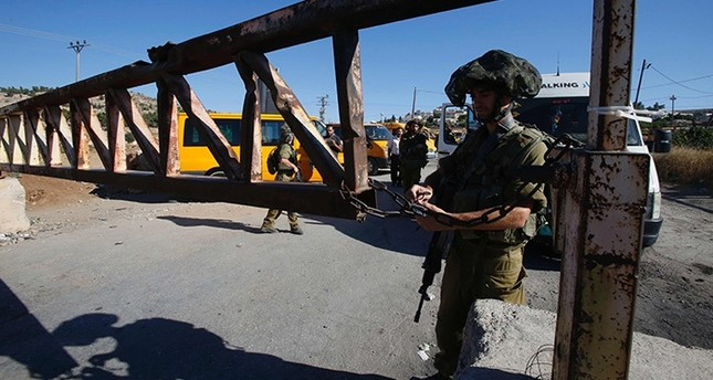 Israeli soldiers open a barrier blocking access to the al-Fawwar refugee camp, south of the West Bank city of Hebron, on July 26, 2016. (AFP Photo)
