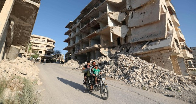 Syrian men ride a motorcycle past heavily damaged buildings in the opposition-held town of Maaret al-Numan in the north of Idlib province on Sept. 27.