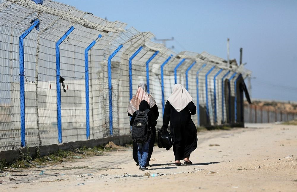 Palestinian women living near Erez crossing point walk near the border after its closure from the Palestinian side in the town of Beit Hanun in the northern Gaza Strip, March 26.