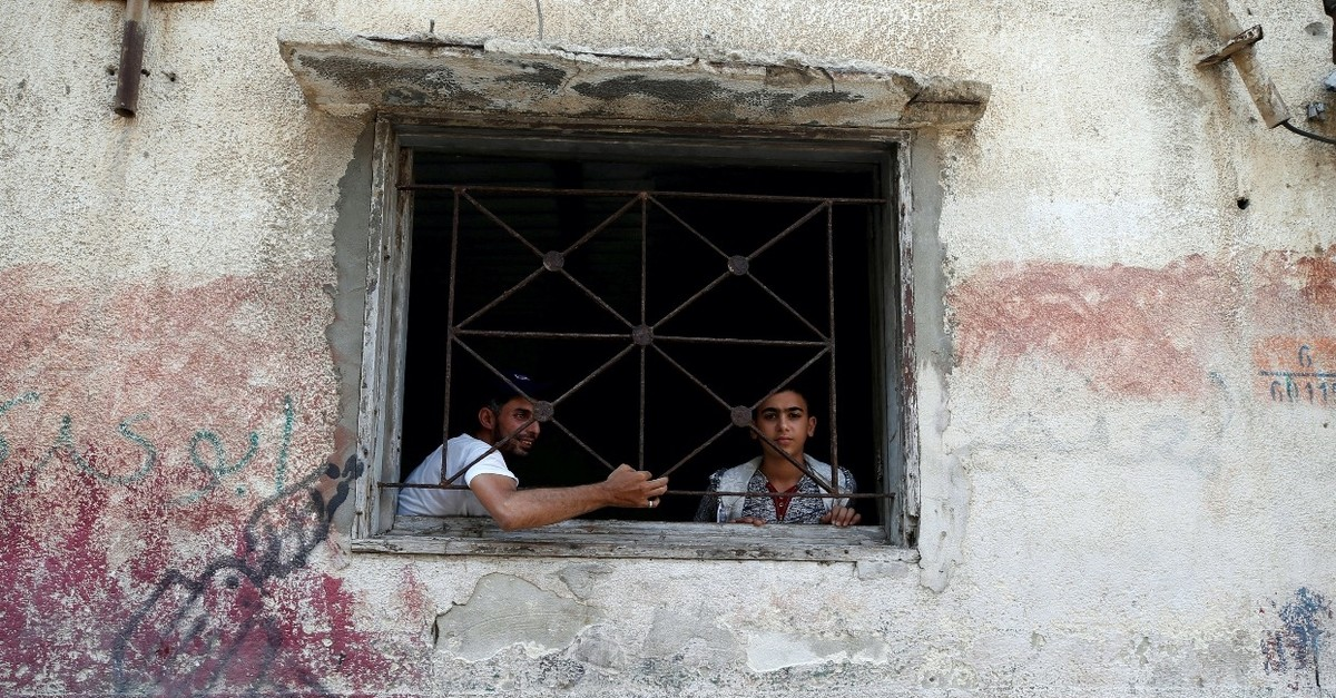 Palestinians look out of their home at al-Shati refugee camp in Gaza city, Sept. 3, 2018.