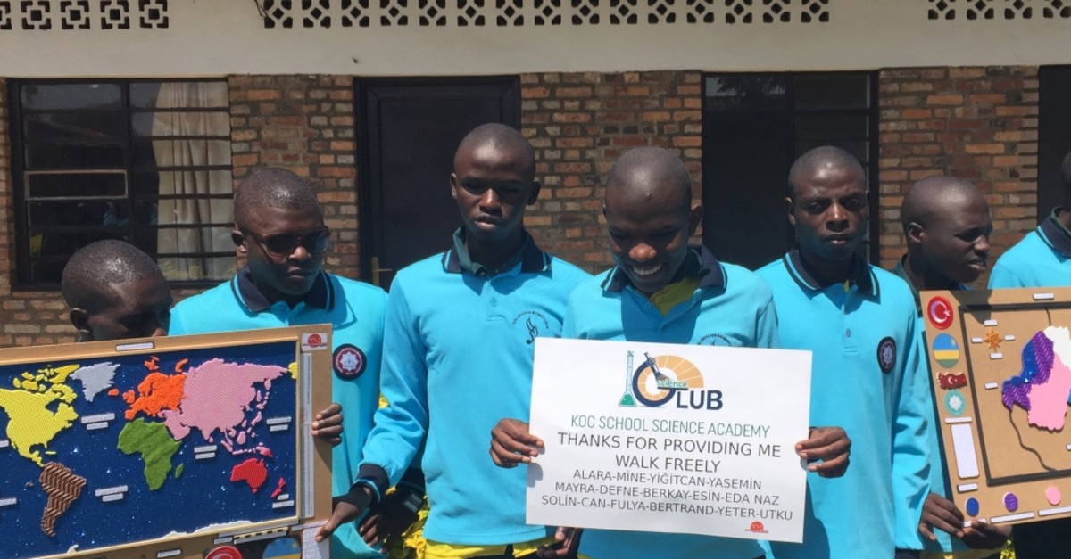 Students in Rwanda display educational materials and a thank you note for Turkish students.