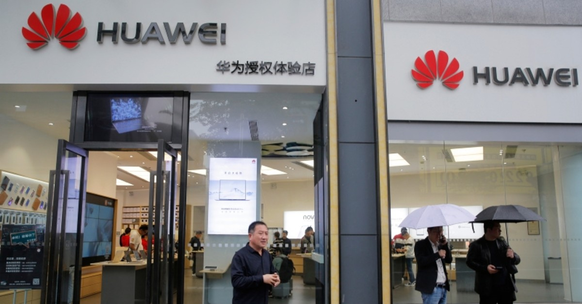 People walk past a Huawei retail shop in Shenzhen, China's Guangdong province, Thursday, March 7, 2019. (AP Photo)