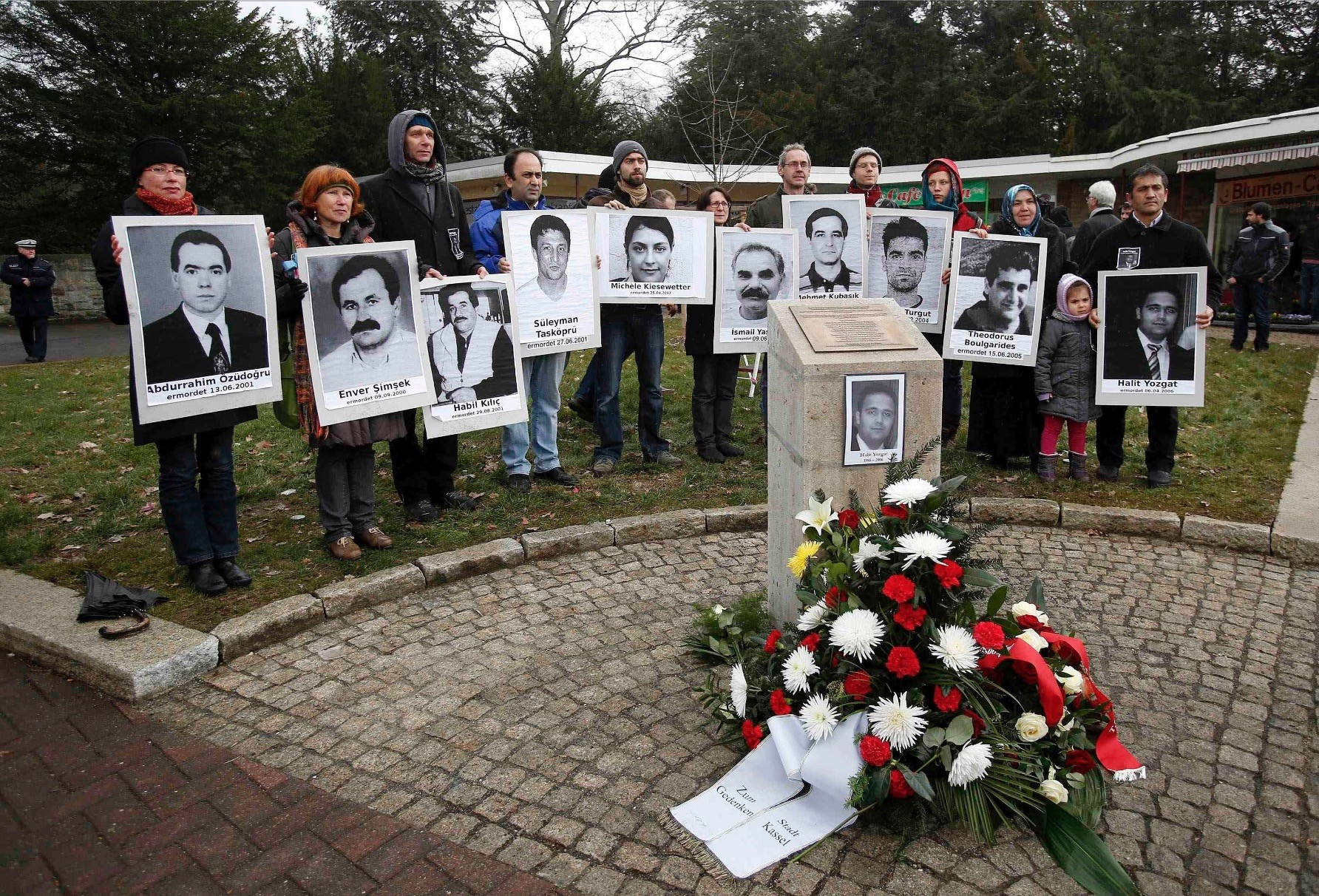People holding photos of NSU victims around a monument dedicated to the gangu2019s last Turkish victim Halit Yozgat in a 2015 commemoration ceremony.