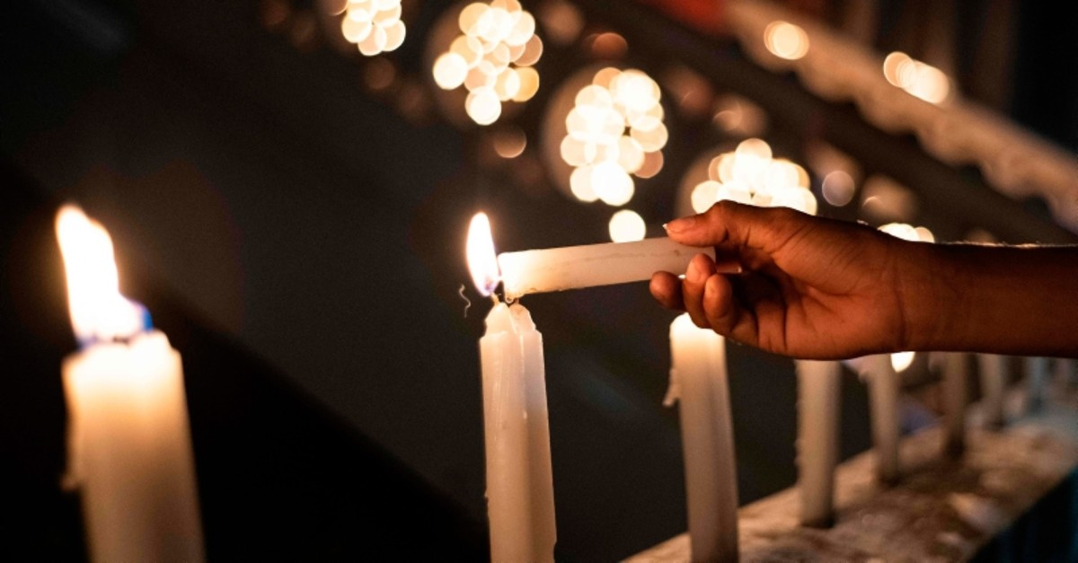 A mourner lights candles during a vigil in memory of the victims in Colombo on April 28, 2019, a week after a series of bomb blasts targeting churches and luxury hotels on Easter Sunday in Sri Lanka. (AFP Photo)