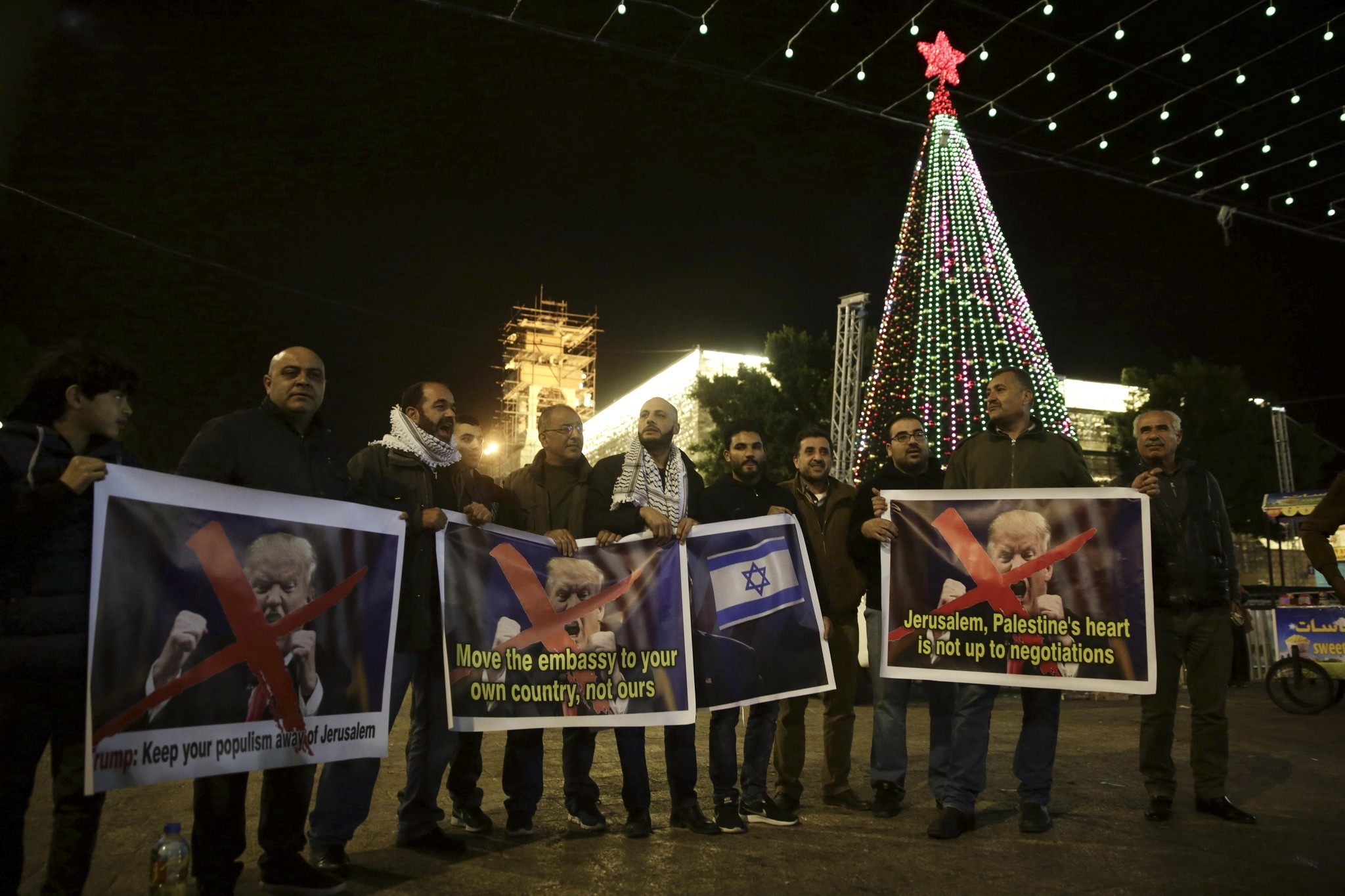 Palestinians hold posters of the U.S. President Donald Trump during a protest in Bethlehem, West Bank, Tuesday, Dec. 6, 2017. (AP Photo)