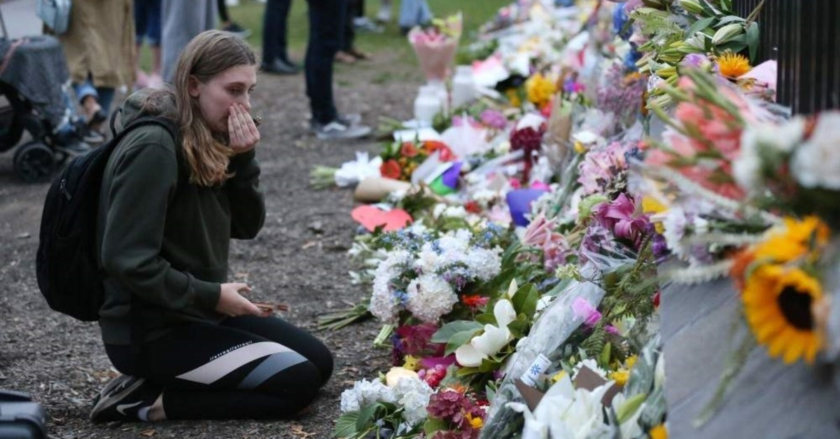 People pay their respects in front of floral tributes for victims of the mosque attacks, Christchurch, March 16, 2019. (AFP Photo)