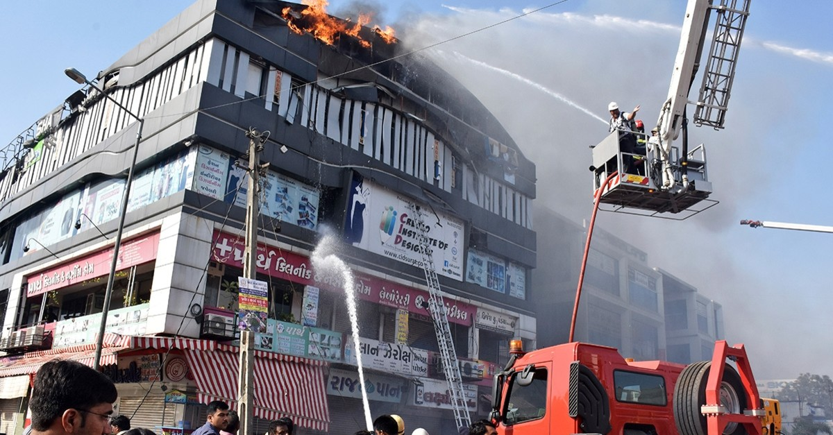 Firefighters work to douse flames on a building in Surat, in the western Indian state of Gujarat. (AP Photo)