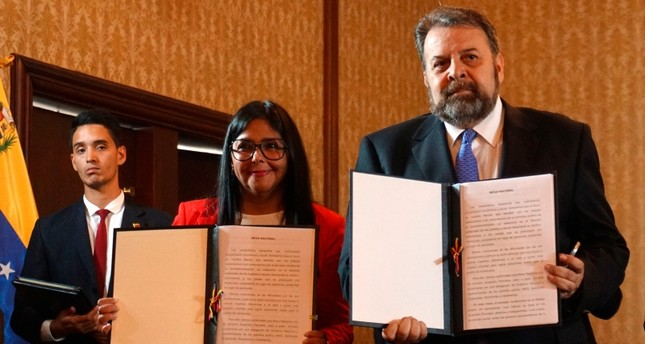 Handout picture from Venezuela's Foreign Ministry press office shows Vice-President Delcy Rodriguez L and opposition deputy Timoteo Zambrano R after signing an agreement for the government's return to Parliament, in Caracas, Sept. 16, 2019. AFP