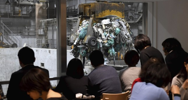 Customers watching an enormous crane pick up rubbish for incineration at a combustible waste pit at the Gomi Pit bar in Tokyo.