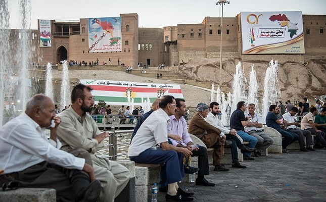 This file photo shows people sitting in a central square in KRG capital Irbil with the city's historic citadel seen in the background, on Sept. 25, 2017. (Photo: Yunus Paksoy / Daily Sabah)