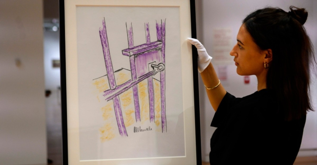 A worker holds a sketch by Nelson Mandela -- ,The Cell Door, Robben Island, -- on April 26, 2019 in New York City. (AFP Photo)