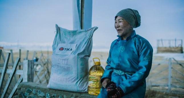 A Dukha woman sits next to food distributed by TİKA in Tsagaannuur, Feb. 27, 2019.