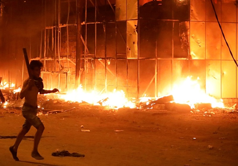 A protestor passes by a burning building in Basra, southeast of Baghdad, Iraq, Thursday, Sept. 6, 2018. (AP file photo)