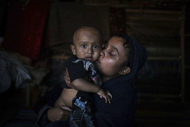 In this Nov. 27, 2017, photo, Asmida 20, kisses her 9 month-old son, Mohamed Umair in a friend's tent in Kutupalong refugee camp in Bangladesh. (AP Photo)