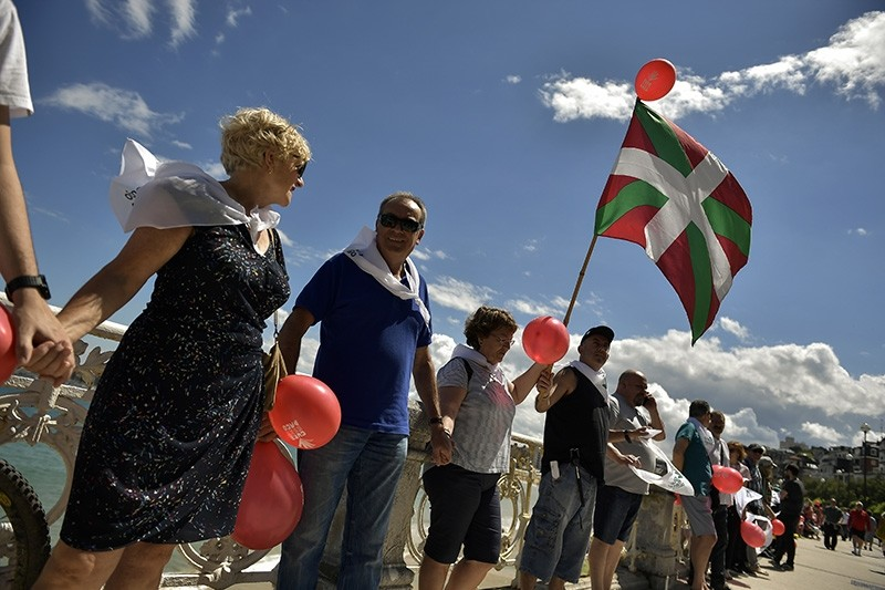 A man holds up a Basque flag as people gather along La Concha beach, while thousands of independence demonstrators make a human chain calling for the independence of the Basque Country, in San Sebastian, Spain, June 10, 2018. (AP Photo)