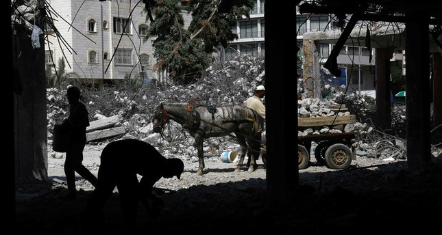 Palestinian workers remove debris from buildings which were destroyed during the 50-day war between Israel and Hamas militants in the summer of 2014, in Gaza City, on August 10, 2016.emAFP Photo/em