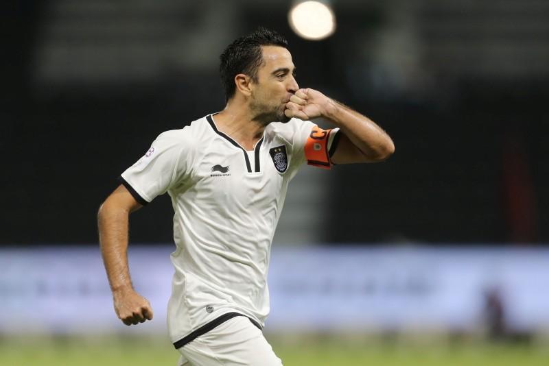 Qatari Al-Sadd club's Xavi Hernandez celebrates scoring a goal against Al-Rayyan's team during their Qatar Stars League football match at the Jassim Bin Hamad stadium in Doha. (AFP Photo)