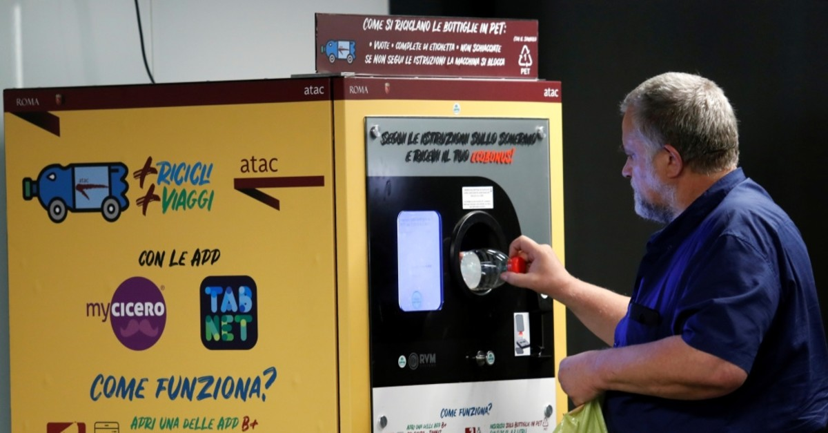 A man puts a plastic bottle into a recycling machine in San Giovanni metro station in Rome, Italy.