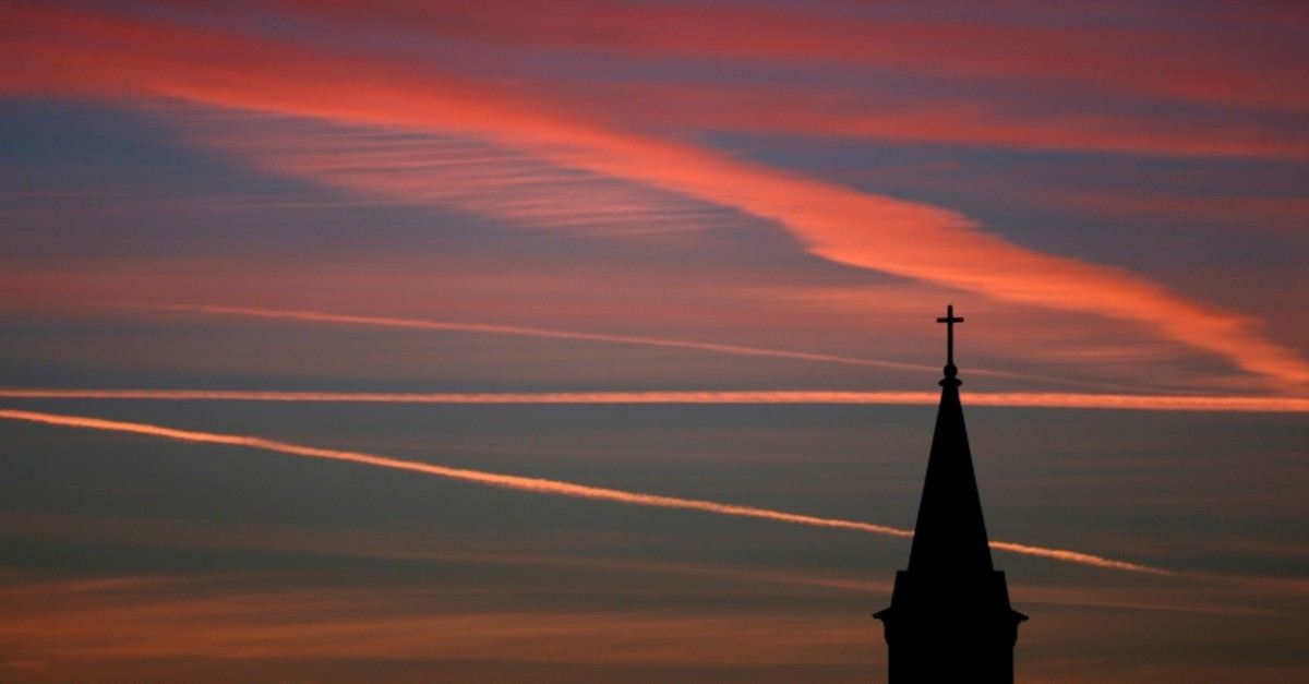 In this Saturday, Jan. 18, 2014 file photo, contrails from jets glow pink as they are illuminated by the setting sun in the skies beyond a church in Kansas. (AP Photo)