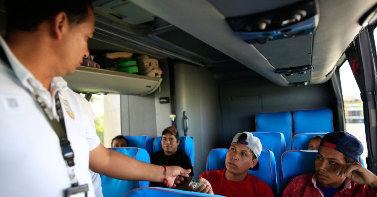 An officer from the National Migration Institute checks travelers' IDs aboard a northbound bus at a checkpoint outside Tapachula, Mexico, Wednesday, June 12, 2019. (AP Photo)