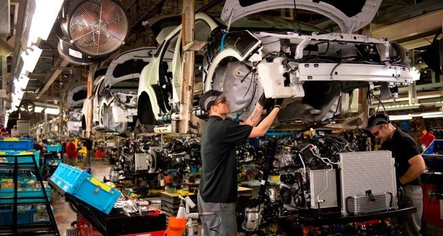 In this file photo taken on November 12, 2014 A member of Nissan's manufacturing staff works in the 'Trim and Chassis' section of their Sunderland Plant in Sunderland, North East England on November 12, 2014. (AFP Photo)