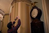 الصحفيون يراقبون ساعة في إحدى ردهات مبنى الكونغرس