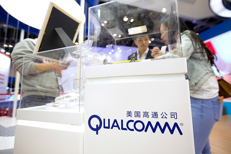 In this Thursday, April 27, 2017 file photo, visitors look at a display booth for Qualcomm at the Global Mobile Internet Conference (GMIC) in Beijing, China. (AP Photo)