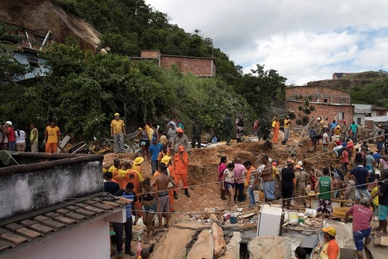 Residents, volunteers and firefighters work over the debris after a mudslide in Boa Esperanca or ,Good Hope, shantytown in Niteroi, Brazil, Saturday, Nov. 10, 2018. (AP Photo)