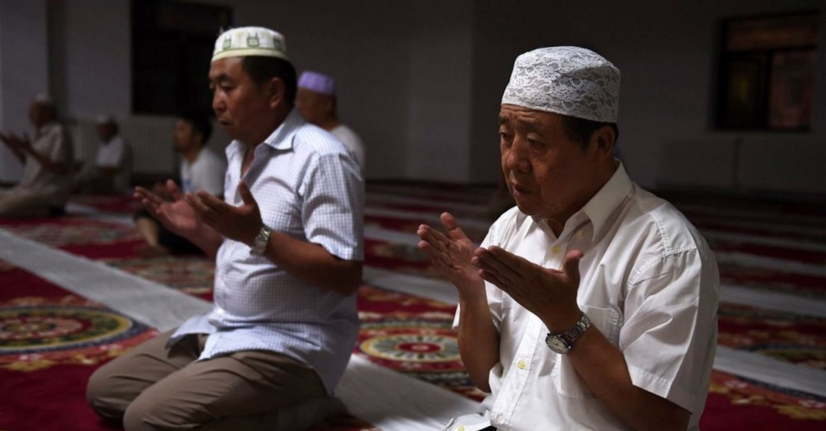 Two Uighurs pray in a mosque in Xinjiang where the oppressive policies of the Chinese government toward the Uighur minority have drawn criticism from the international community.