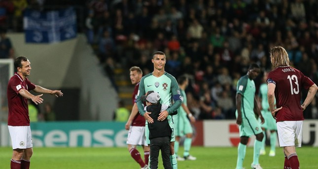 A boy hugs Portugal's player Cristiano Ronaldo after the 2018 FIFA World Cup qualifier soccer match be-tween Latvia and Portugal in Riga, Latvia, 09 June 2017. (EPA Photo)