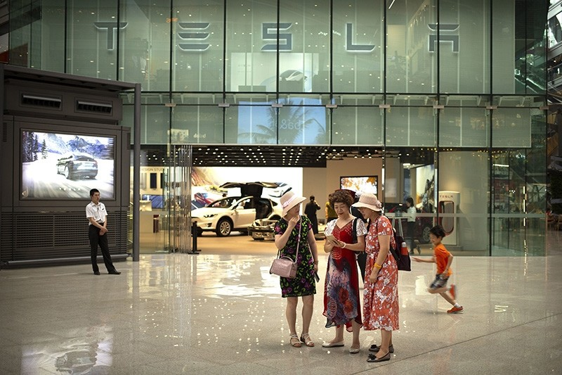 In this July 5, 2018, file photo, women look at a smartphone outside of a Tesla showroom at an upscale shopping mall in Beijing. (AP Photo)