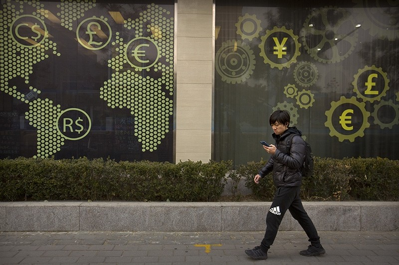 A man looks at his smartphone as he walks past a display showing symbols for world currencies on the exterior of a bank in Beijing, Thursday, Dec. 14, 2017. (AP Photo)