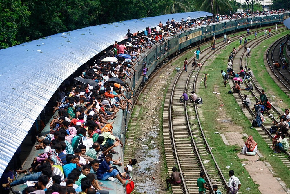 People overload the roof of a train as they travel to their villages ahead of the Eid celebrations in Bangladesh