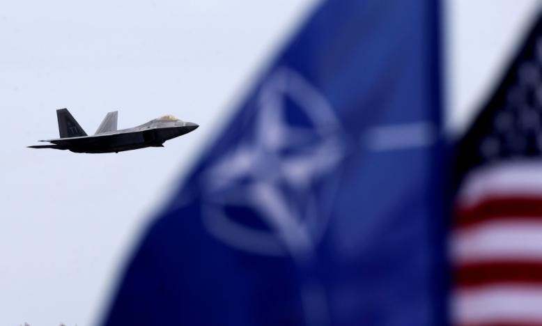 NATO and U.S. flags flutter as U.S. Air Force F-22 Raptor fighter flies over the military air base in Siauliai, Lithuania, April 27, 2016. (Reuters Photo)