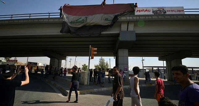 People hang a large Iraqi flag off a bridge in Kirkuk, Iraq, Oct. 16, 2017. (Reuters Photo)