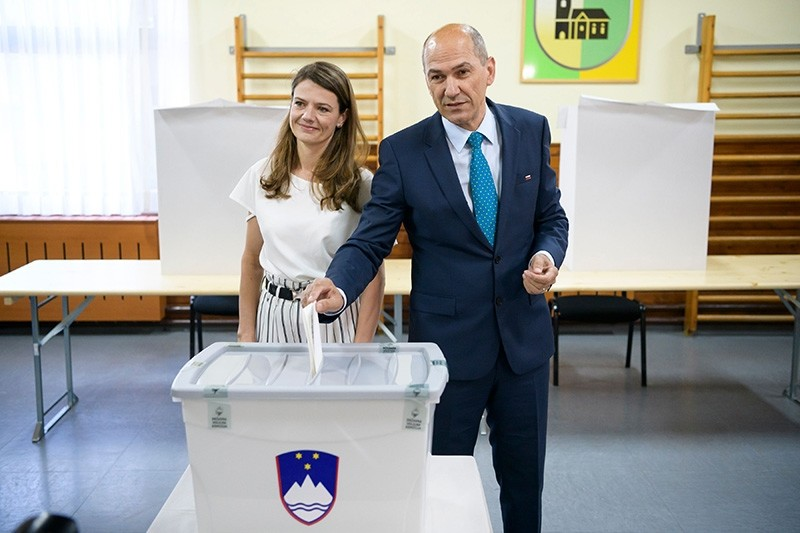 Janez Jansa (R), former Slovenian Prime Minister and President of Slovenian Democratic Party (SDS), flanked by his wife Urska Bacovnik (L), casts his ballot at a polling station in a small village Sentilj, Slovenia, on June 3, 2018. (AFP Photo)
