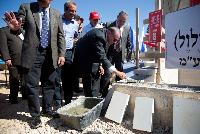 U.S. Governor Mike Huckabee, centre, lays a brick at a new housing complex in the West Bank settlement of Efrat, Wednesday, Aug. 1, 2018. (AP Photo)