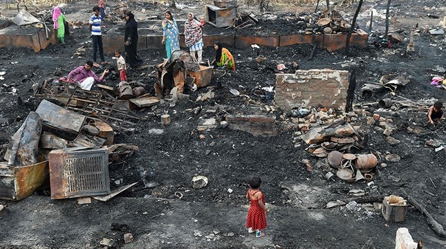 Rohingya refugees look for their belongings in New Delhi on April 16, 2018, following a fire that broke out at their camp early April 15 that left around 200 people homeless. AFP Photo