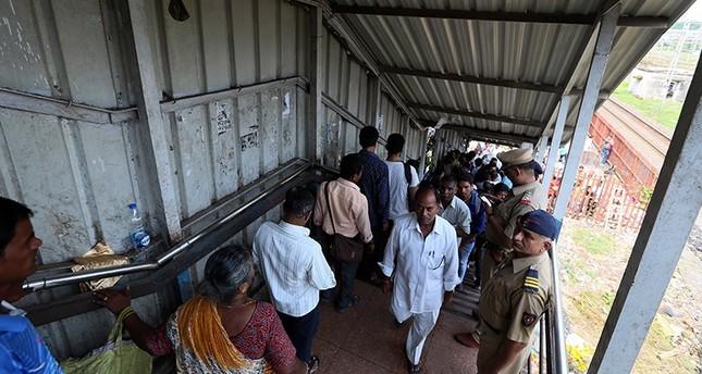 Commuters walk on foot overbridge at Elphinston Road railway station in Mumbai, India, 29 September 2017 (EPA Photo)