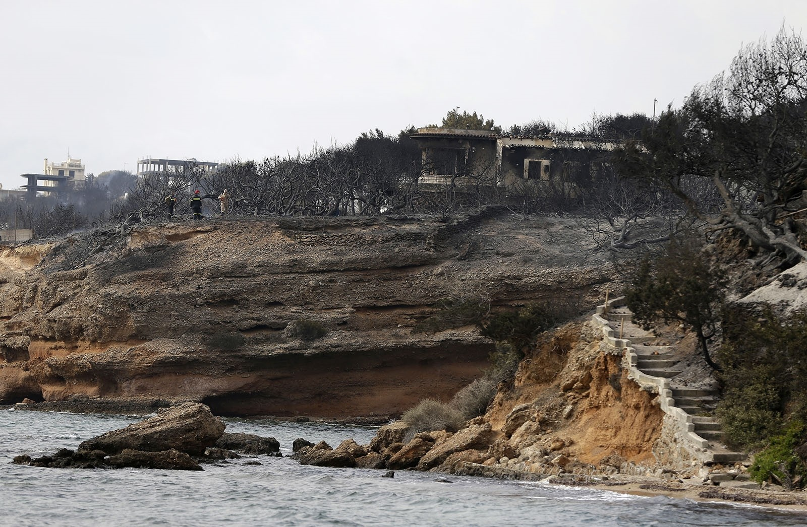 Firefighters stand on a cliff top where burned trees hug the coastline in Mati east of Athens, Tuesday, July 24, 2018.