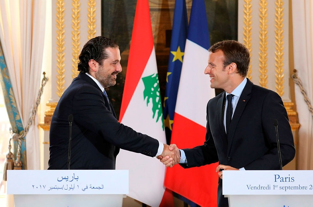 This file photo taken Sept. 1, 2017 shows French President Emmanuel Macron (R) shaking hands with Lebanese Prime Minister Saad Hariri during a press conference at the Murat Lounge in the Elysee Palace in Paris, France. (AFP Photo)