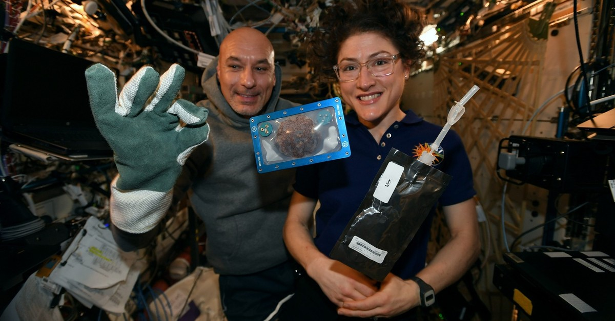 US astronaut Christina Koch and Italian astronaut Luca Parmitano pose for a photo with a cookie baked on the International Space Station (Photo from Twitter)