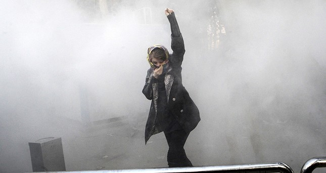In this Dec. 30, 2017 photo, a university student attends a protest inside Tehran University while a smoke grenade is thrown by Iranian police, in Tehran, Iran. (AP Photo)