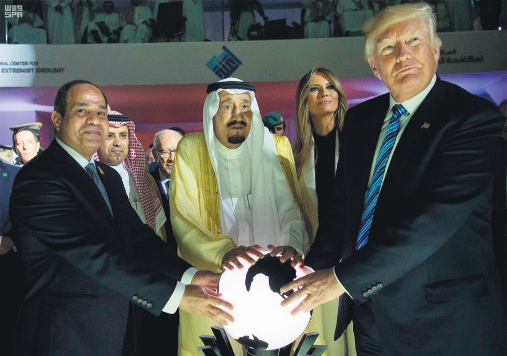 Egypt's coup leader and President Sissi (L), Saudi King Salman (C) and U.S. President Trump (R) place their hands on a globe during a Riyadh meeting that is claimed to have played a big role in the recent decision to isolate Qatar.