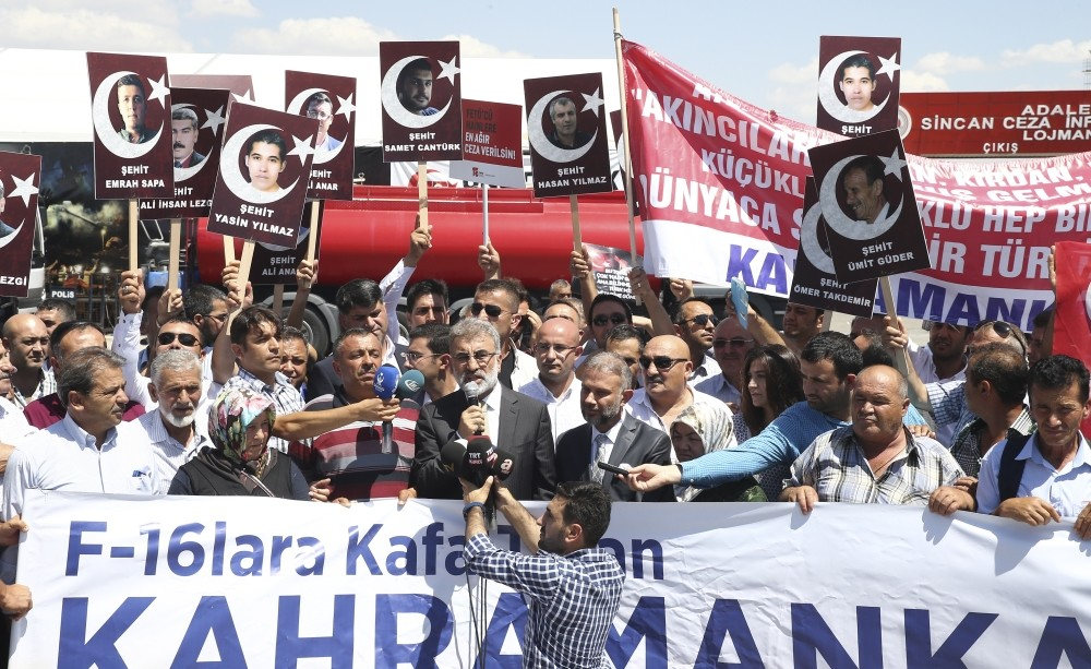 Protesters hold photos of people killed outside Aku0131ncu0131 Air Base on July 15, 2016, while AK Party lawmaker Taner Yu0131ldu0131z speaks in front of the courthouse where the coup suspects are on trial in Ankara.