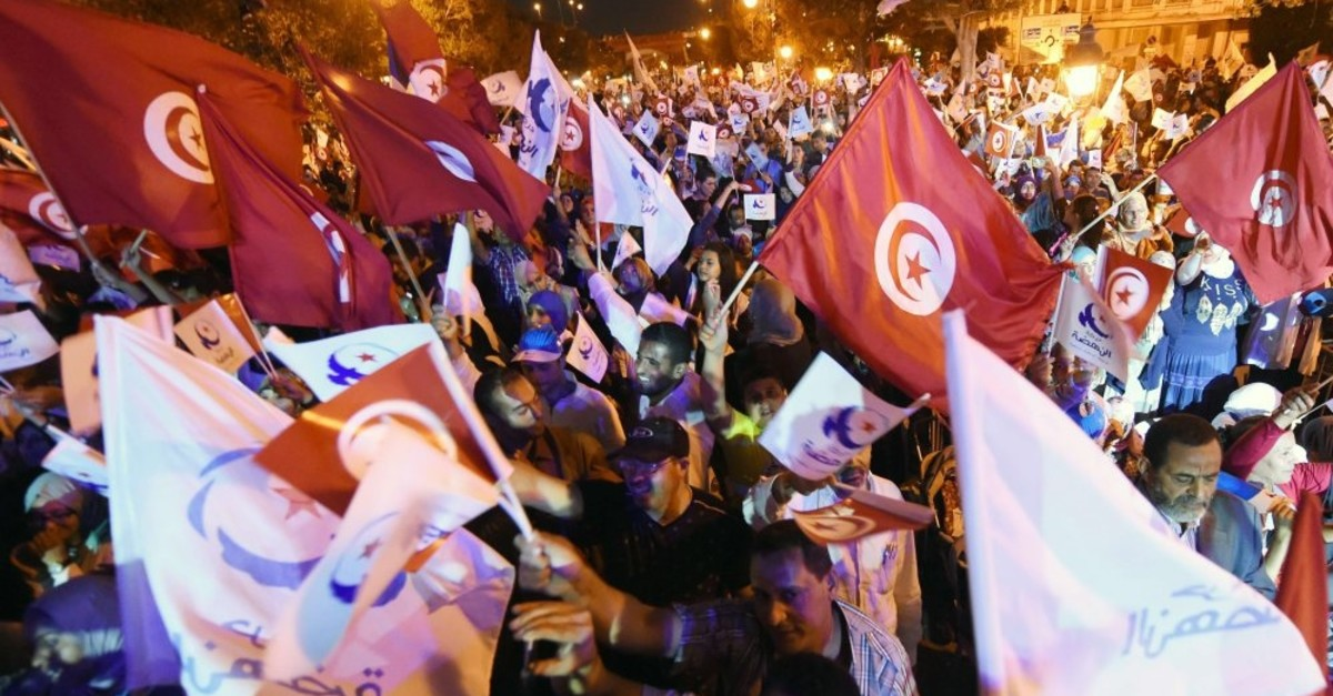 Supporters wave the flags of Tunisia and the Ennahda movement during a campaign rally, Tunis, Oct. 24, 2014.